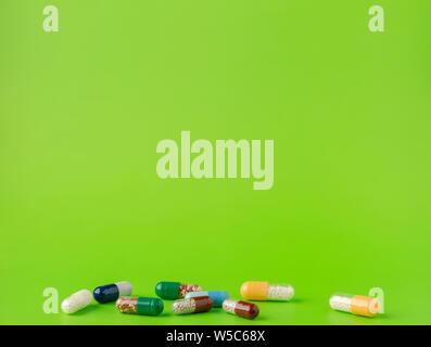 Verschiedene Blau, Weiß, Braun, Grün und Gelb Kapseln mit anderen Arzneimitteln, mikrogranulate auf grünem Hintergrund.