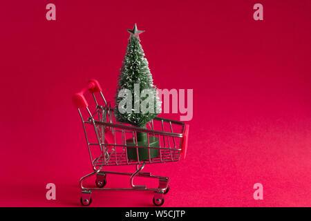 Kleine weihnachtskugel Weihnachtsbaum in einem Warenkorb auf einem rosa Hintergrund, Weihnachten und Neujahr Grußkarte mit Kopie Raum - Stockfoto