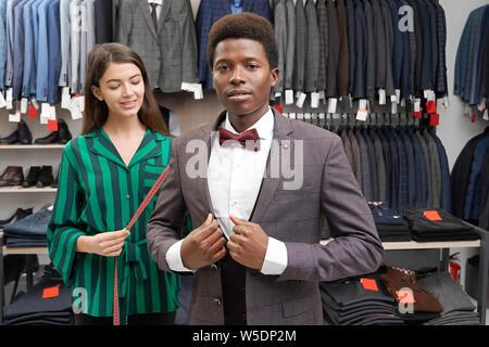 Junge, afrikanische Mann mit lockigem Haar in Boutique Verschraubung grauen Anzug. Recht shop Berater holding Maßband. In weißem Hemd, Weste, Jacke und roter Schleife binden Kunden an Kamera suchen. - Stockfoto