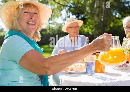 Senioren mit Picknick im Freien bei Sonnenschein, blonde schöne Frau mit Hut ist mit Orangensaft zu alten Freunden. - Stockfoto