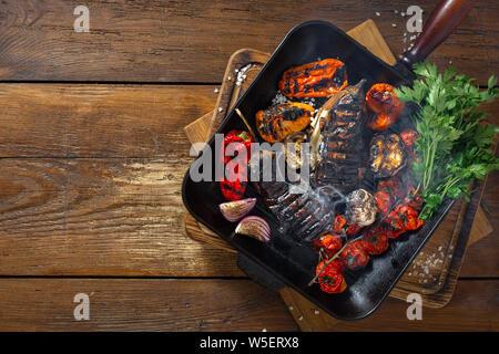 Verschiedene Gemüse auf dem Grill Pfanne auf einem hölzernen Hintergrund der Ansicht von oben zubereitet - Stockfoto