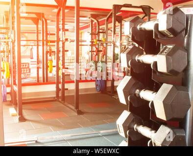 Rack mit Hanteln in den modernen Fitnessraum gegen das Fenster mit dem Sonnenuntergang, kopieren Raum - Stockfoto