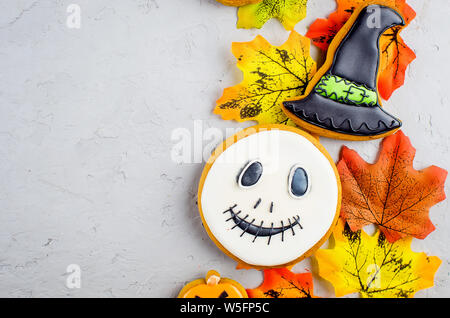 Halloween Hintergrund mit Lebkuchen cookies, Kürbis, Süßigkeiten und Blätter im Herbst auf grauem Beton Hintergrund, Kopieren, Ansicht von oben, flach, Mock - Stockfoto