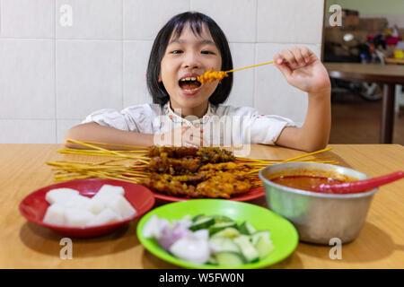 Asiatische kleinen chinesischen Mädchen essen Satay auf ein Restaurant im Innenbereich - Stockfoto
