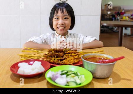 Asiatische kleinen chinesischen Mädchen essen Satay auf ein Restaurant im Innenbereich