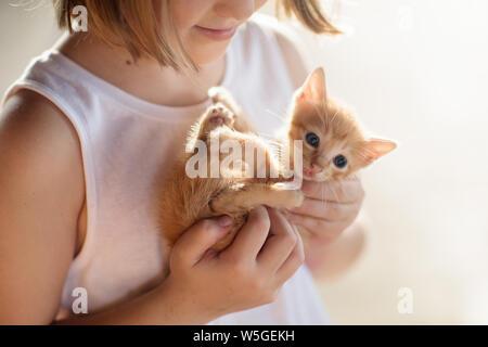 Kind Holding Baby Katze. Kinder und Haustiere. Kleines Mädchen umarmt niedlichen kleinen Kätzchen im Sommer Garten. Haustier in der Familie mit Kindern. Kinder mit hom