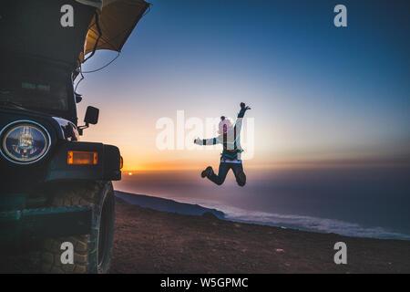 Reisen und der Suche nach Glück für Menschen - Frau aus Zurück springen und genießen Sie die Freiheit und den wunderschönen Sonnenuntergang am Berg top-Auto mit - Stockfoto