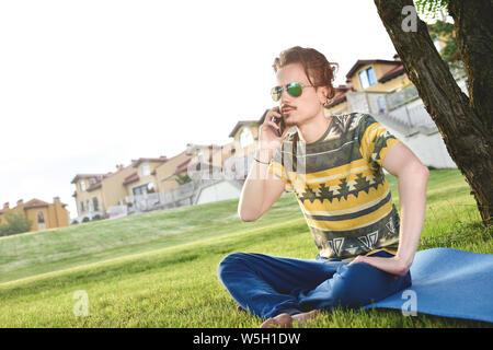 Junge stilvolle hübscher Kerl sitzt auf Gras und Telefonieren im Park ausruhen. Pause - Stockfoto