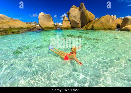 Glückliche Frau im Bikini liegen in türkisfarbenem Wasser im natürlichen Pool der Seychellen Strand Anse Marron, La Digue, Seychellen, Indischer Ozean, Afrika - Stockfoto