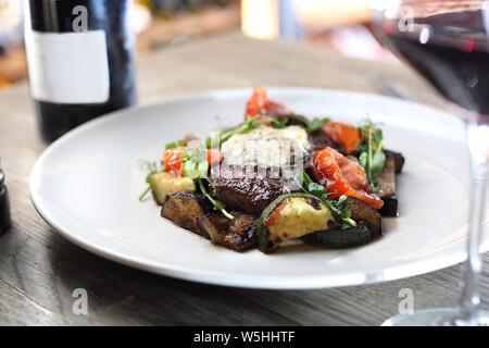 Gegrilltes Steak von entrecote mit Kräuterbutter und gegrilltes Gemüse auf einem weißen Teller serviert. - Stockfoto