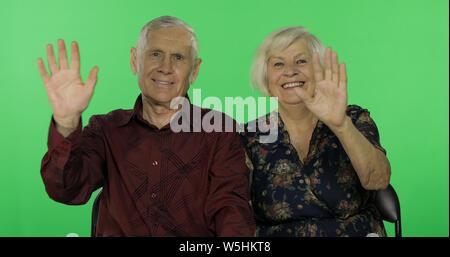 Senior im Alter von Mann und Frau Winken mit der Hand auf die Kamera unter Chroma Key Hintergrund. Konzept einer glücklichen Familie im Alter. Für ihr Logo oder Text platzieren. Grüner Hintergrund - Stockfoto