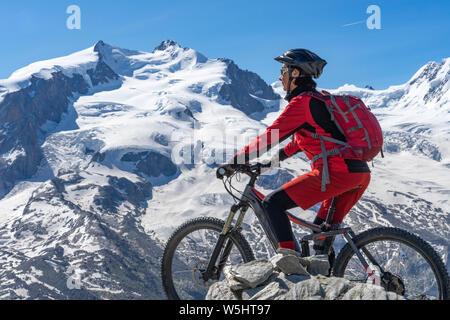 Active Senior, Frau, reiten Ihr elektrische Mountainbike auf dem Gornergrat bei Zermatt, Wallis, Schweiz. Im Hintergrund Gornergletscher, Monte Rosa - Stockfoto