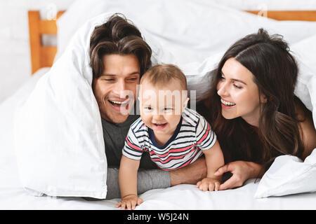 Fröhliche Eltern spielen mit Baby Sohn im Bett