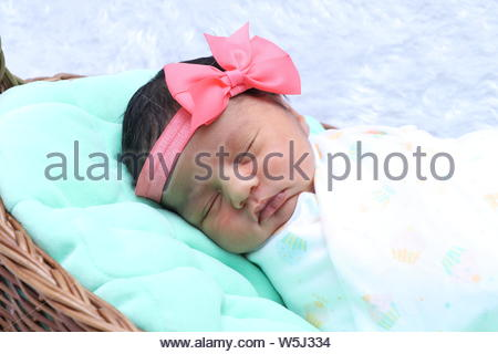 Cute Baby Mädchen mit Stirnband und Schlafen in Korb - Stockfoto