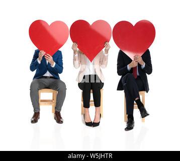 Zwei Männer und eine Frau, die ihre Gesichter mit großen roten Herzen beim Sitzen auf Stühlen auf weißem Hintergrund - Stockfoto