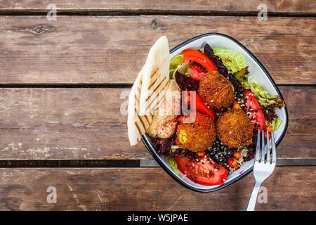 Israelische Street Food. Falafel mit Hummus, Rote-Bete-Salat und Gemüse in einer Schüssel in ein Restaurant.