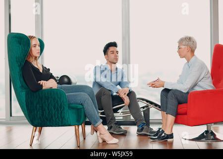 Junger Mann und Frau sind chatten, während in einem Stuhl sitzen. Brainstorming Konzept. - Stockfoto