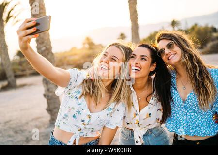 Gruppe von drei Frauen, die Freunde einen selfie in einem Strand bei einem Sommertag. Freundschaft und Urlaub. - Stockfoto
