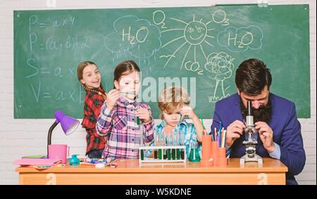 Beobachten Sie die Reaktion. Wissenschaft ist immer die Lösung. Schule Chemie Experiment. Erklären der Chemie zu Kindern. Faszinierende Chemie Lektion. Man bärtige Lehrer und Schüler mit Reagenzgläsern im Klassenzimmer. - Stockfoto