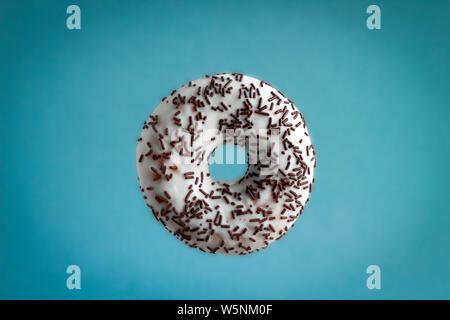 Süße Krapfen mit weißer Schokolade und Pralinen besprüht Fliegen auf blauem Hintergrund - Stockfoto