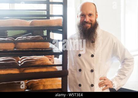 Portrait von zufriedenen jungen Erwachsenen Bäcker mit langen Bart in weiße Uniform stehend an seinem Arbeitsplatz, in der Nähe der Regale mit Brot in der Bäckerei manufacturin - Stockfoto