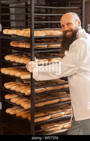 Portrait von Freude junger Erwachsener Bäcker mit langen Bart in weiße Uniform stehend in der Nähe der Regale voll mit frisch gebackenen Plätzchen in seinem Arbeitsplatz, ICH - Stockfoto