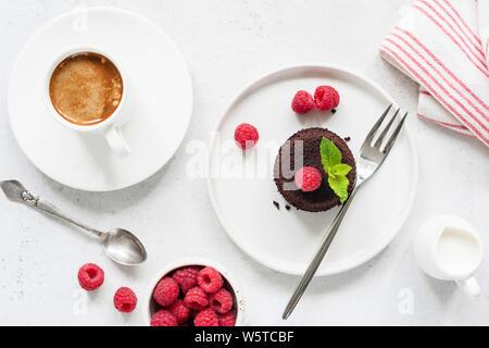 Schokoladentorte mit Himbeeren und Tasse Espresso Kaffee auf weißem Beton Tabelle Hintergrund serviert. Ansicht von oben - Stockfoto