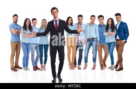 Lächelnd Geschäftsmann team leader empfängt Sie mit beiden Händen in seine beiläufige Team beim Stehen auf weißen Hintergrund. Er trägt einen schwarzen Anzug und die - Stockfoto