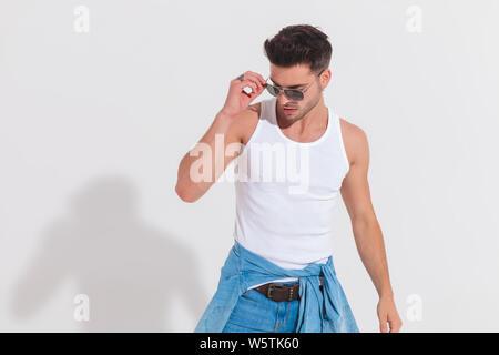 Legerer Mann im Studio Light fixes Sonnenbrille und blickt zur Seite stehend, portrait Bild - Stockfoto