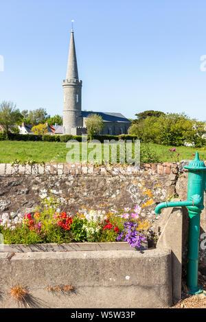 Blumen in einem alten Wassertrog neben einer Pumpe in Torteval Guernsey, Channel Islands, Großbritannien