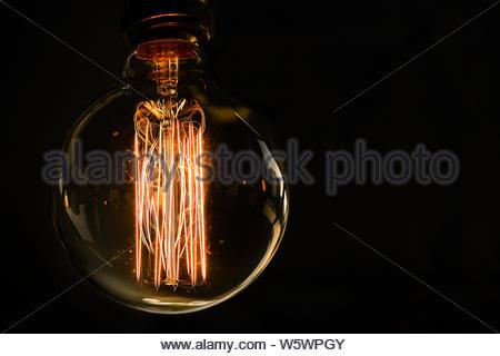 Glas retro Glühbirne Edison auf einem dunklen Hintergrund. Designer Licht und Beleuchtung der Innenräume. - Stockfoto