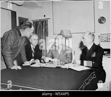 Präsident Harry S. Truman erhält den aktuellen Wetterbericht Als erörtert er die Vorbereitungen für die Potsdamer Konferenz mit Außenminister James Byrnes (zweiter von links) und Adm. William Leahy (ganz rechts). Sie sind an Bord der US S. Augusta. - Stockfoto