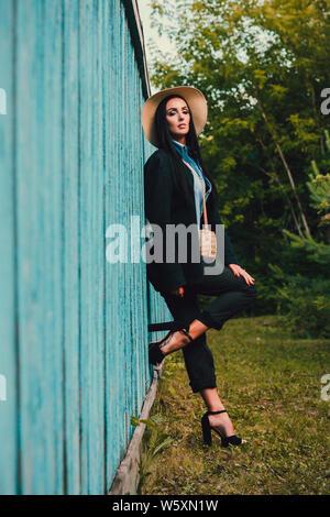 Tom Sawyer hübsche Frau in der strohhut stand vor der Zaun. Die Frau malte ein Holzzaun. - Stockfoto