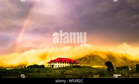 Eine fantastische am frühen Morgen in der Dämmerung mit einem leichten Regenbogen und einem hellen roten Dach Gebäude - auf meinem Weg, um zu sehen, 'Welten', Horton Plains, Sri Lanka. - Stockfoto