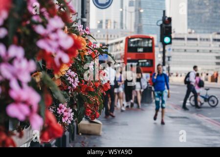 Unbekannte Menschen zu Fuß auf einer Straße in London, UK, vorbei am Gebäude mit blühenden Blumen. Selektiver Fokus, das Leben in der Stadt. - Stockfoto