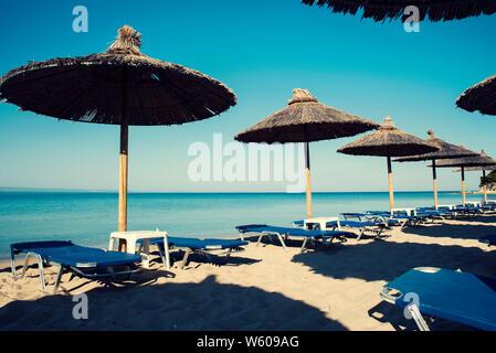 Eine Zeile mit dem Stroh Schirme an einem schönen Strand in Griechenland und keine Leute selektiven Fokus - Stockfoto
