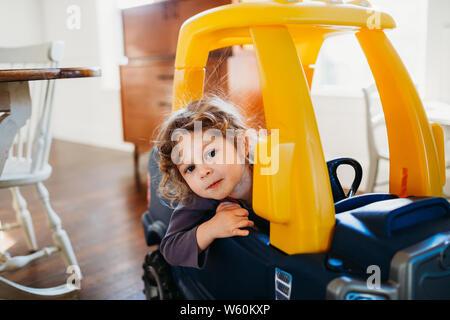 Junge Mädchen an der Kamera in Spielzeug Auto sitzen innen Esszimmer suchen