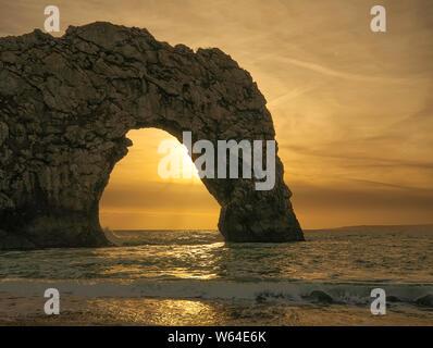 Durdle Door bei Sonnenuntergang. Natürlicher Kalkstein Bogen auf Jurassic Küste von Dorset. Auf der Suche nach Westen in Richtung Portland Bill. West Lulworth. Nordsee. UK. Schließen - Stockfoto