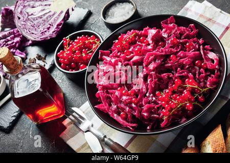 Der dänische Rotkohl schließen gekocht mit Essig und Rote Johannisbeere Saft in einem schwarzen Schüssel mit geschnittenem Brot auf einen konkreten Tisch serviert. Zutaten - Stockfoto