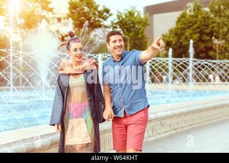 Gerne diverse Paar in Liebe Hände halten einen abendlichen Spaziergang auf Straße der Stadt - liebevolle reifer Mann und junge Frau zusammen gehen - lächelnd husb - Stockfoto