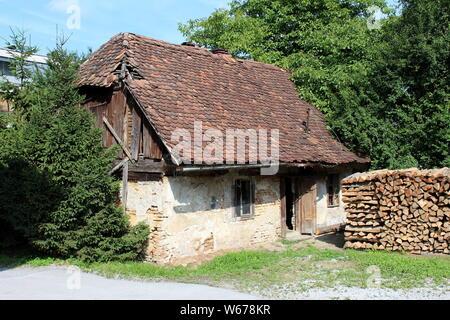 Kleine Familie Haus mit gebrochenen Wänden und marode Fassade mit teilweise fehlende Dachziegel mit dichten Bäumen bedeckt Verlassen - Stockfoto