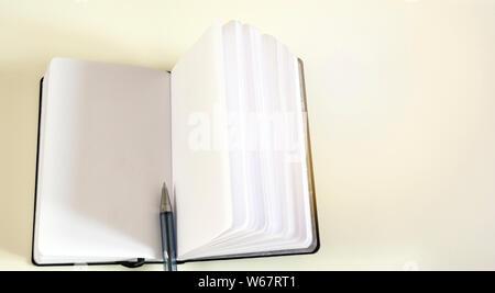 Ein Kugelschreiber in die Mitte eines geöffneten Notebook. Ungeschriebene leeren Seiten. - Stockfoto