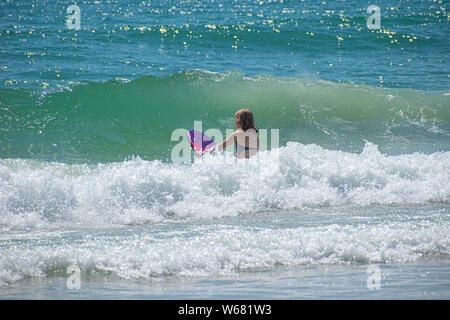 Daytona Beach Florida. Juli 07, 2019 Mädchen mit Surfbrett mit Wellen. - Stockfoto