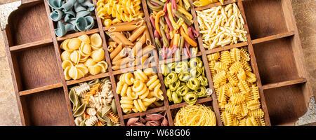 Sortierte bunte italienische Pasta in Holzkiste. Gesundes essen Hintergrund Konzept. Flach, Ansicht von oben. Banner. - Stockfoto