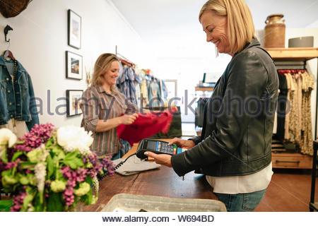 Frau mit Credit Card Reader im shop - Stockfoto