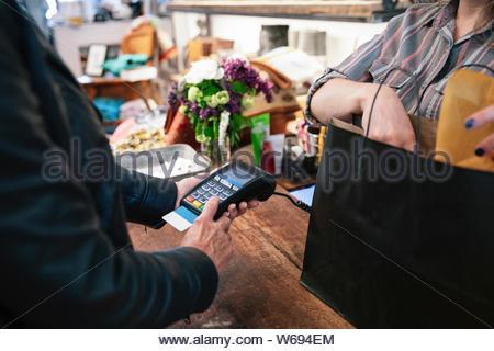 Mann mit Credit Card Reader im shop - Stockfoto