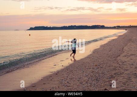 Junge Mädchen am Sonnenuntergang Meer Hintergrund. Glückliches Kind in den Ozean. - Stockfoto