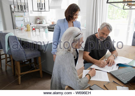 Financial Advisor beobachten senior Paar unterzeichnen Vertrag am Esstisch - Stockfoto
