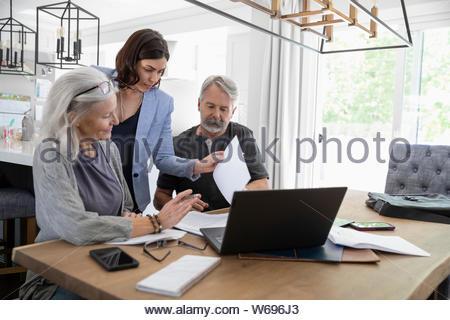 Finanzberater diskutieren Schreibarbeit mit älteren Ehepaar am Esstisch - Stockfoto