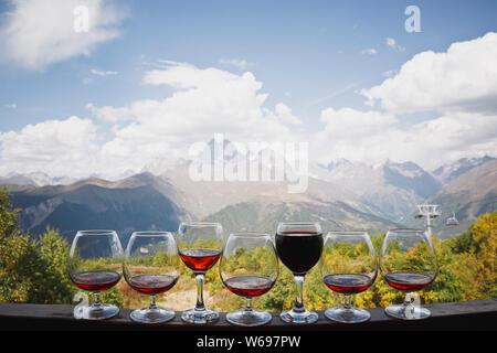 Sechs Gläser cognac und ein Glas Rotwein stand vor dem Hintergrund einer wunderschönen Berglandschaft und die Seilbahn. Es gibt Weisse Wolken in - Stockfoto